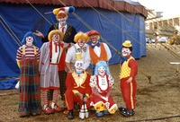 Eight clowns standing in front of circus tent