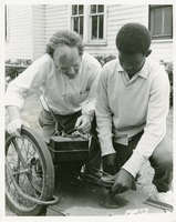 Photograph of Adult and Young Man Fixing a Lawn Mower