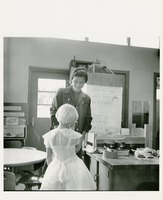 An Adult Smiles at a Young Girl in White Dress