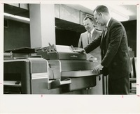 Photograph of Two Men Working a Computer Printer