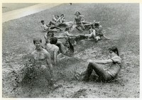 Group of Students Sliding Down a Muddy Hill