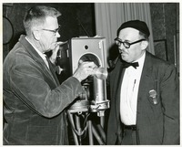 Two Men Inspect an WFSU Camera