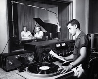 Male Student at a Radio Station, with Two Men in Soundbooth Next to a Piano