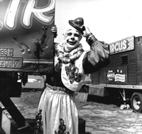 Clown standing near circus caravan