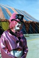 Clown in purple standing in front of circus tent