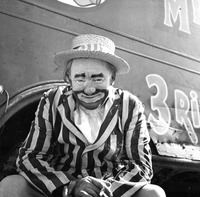 Clown wearing pinstriped jacket