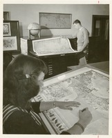 Man and a Woman Looking at Maps