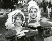 Two Students Wearing Headresses Holding Batons