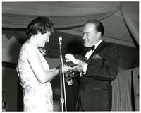 Bob Hope handing Mildred Pepper a flag onstage