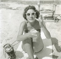 Unidentified Woman Sitting on Towel at Beach